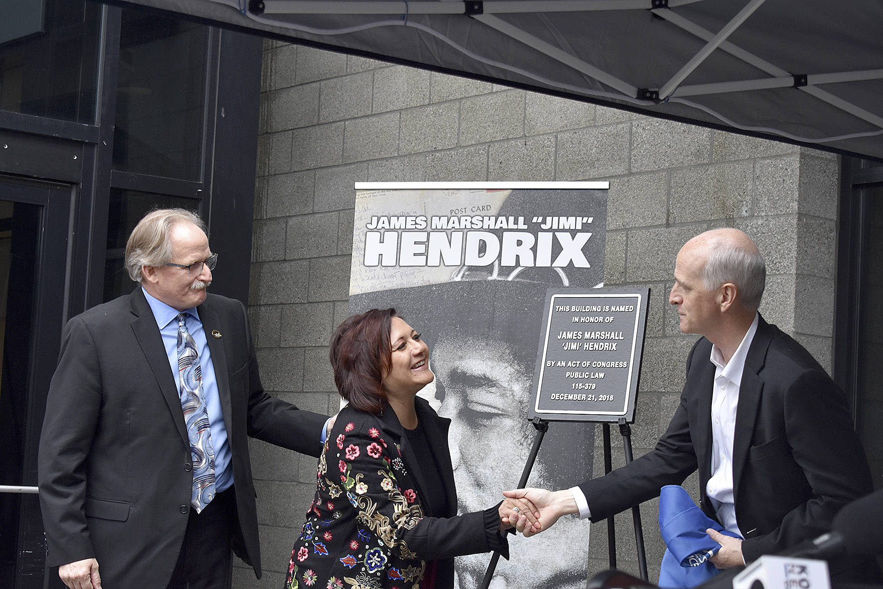 "USPS district manager Darrell Stoke, Janie Hendrix and Congressman Adam Smith (D-WA) unveil the plaque honorarily naming the Renton Highlands Post Office as the ""James Marshall 'Jimi' Hendrix Post Office"" on Friday, April 19. Photo by Haley Ausbun"